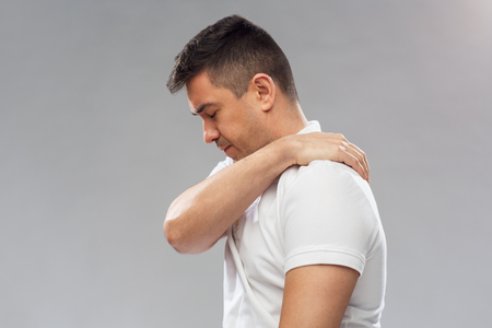 middle joint: people, healthcare and problem concept - unhappy man suffering from pain in shoulder over gray background