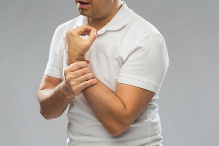 middle joint: people, healthcare and problem concept - close up of man suffering from pain in hand over gray background Stock Photo