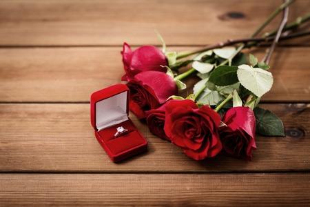uprzejmości: bliska diament pierścionek zaręczynowy i czerwonych róż