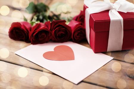 zamknąć pudełko, czerwone róże i kartkę z życzeniami