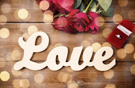 uprzejmości: close up of diamond ring, red roses and word love Zdjęcie Seryjne