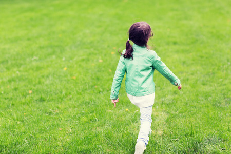 childhood, season ecology and people concept - little girl walking along summer green meadow