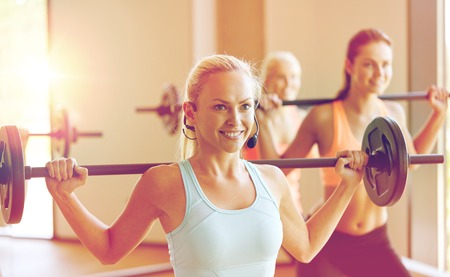 group of women with barbells exercising in gym photo