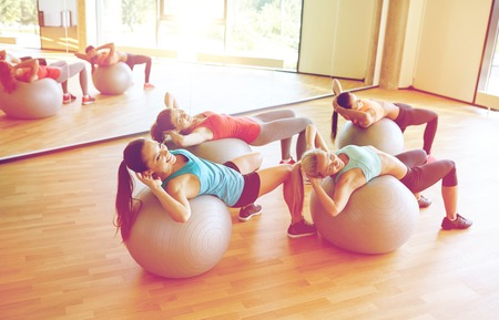 group of women exercising with fit balls in gym photo