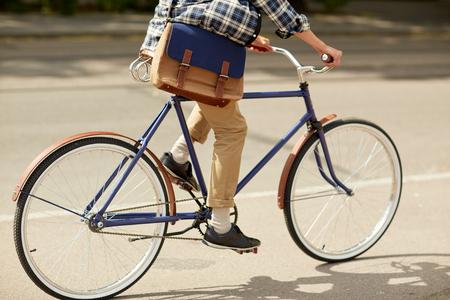 fixed: hombre joven inconformista con la bolsa de montar en bicicleta fija del engranaje