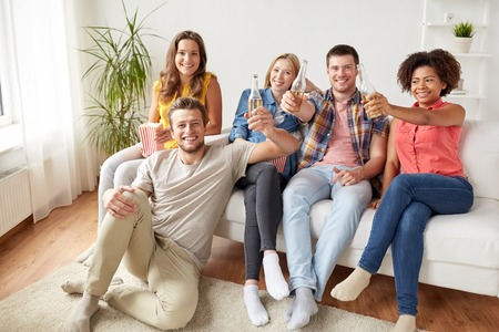 many people: happy friends with popcorn and beer at home Stock Photo