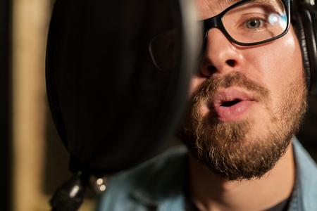 hombre con auriculares cantando en el estudio de grabación