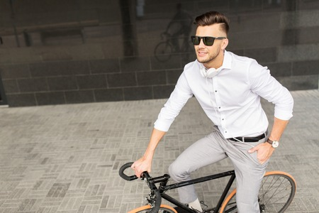young businessman: man with bicycle and headphones on city street Stock Photo