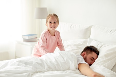 wakening: little girl waking her sleeping father up in bed