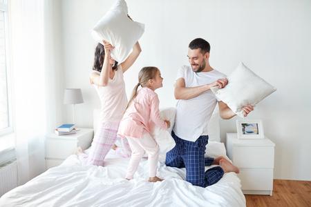 Glückliche Familie, die Kissenschlacht im Bett zu Hause Standard-Bild - 71148969
