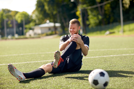 injured soccer player with ball on football field Stockfoto