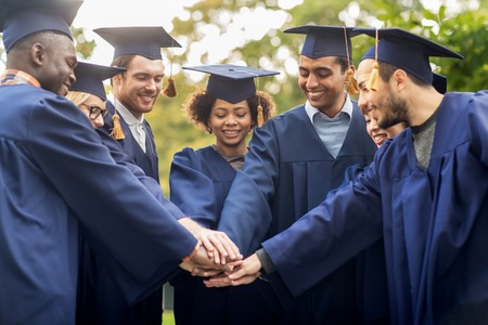 all smiles: happy students in mortar boards with hands on top
