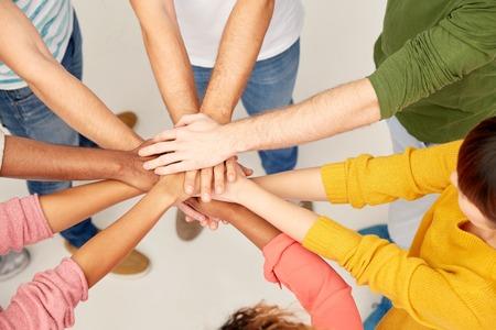 groep van internationale mensen met handen in elkaar