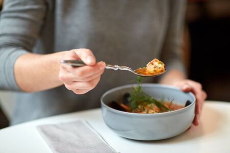 Frau isst Fischsuppe im Café oder Restaurant