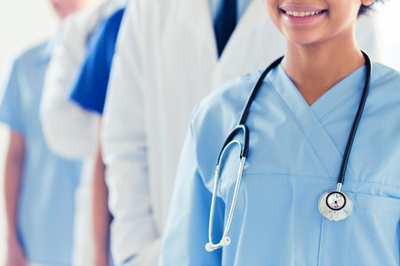 close up of happy doctor or nurse with stethoscope