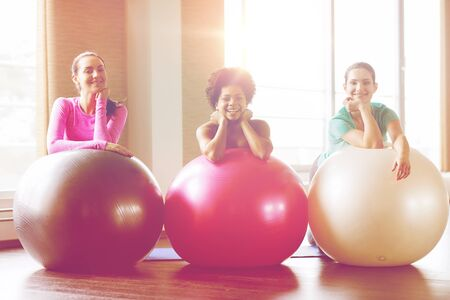 group of smiling women with exercise balls in gym photo