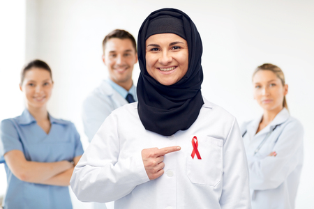 muslim doctor in hijab with red awareness ribbon photo
