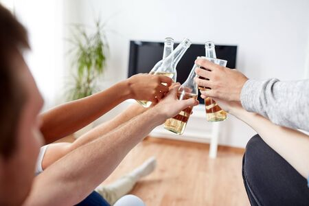 friends clinking beer and watching tv at home