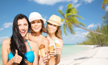 group of happy young women with ice cream on beach