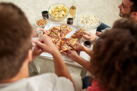 eating fast food: happy friends with drinks eating pizza at home