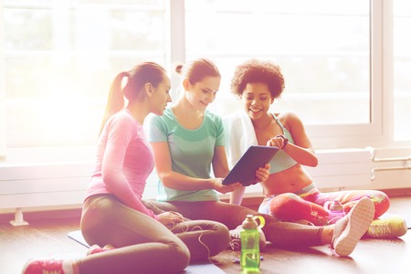group of happy women with tablet pc in gym photo