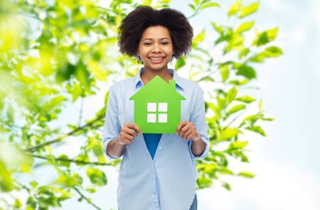 nice accommodations: happy african american woman with green house icon Stock Photo