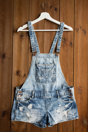 fashion dress: denim or jeans overalls with hanger on wood
