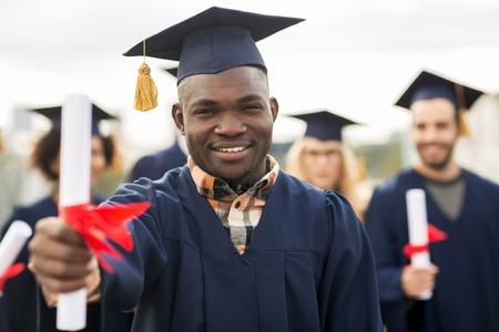 gelukkig studenten in mortel platen met diploma Stockfoto