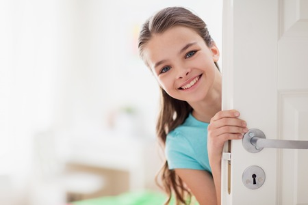 happy smiling beautiful girl behind door at home Stock Photo