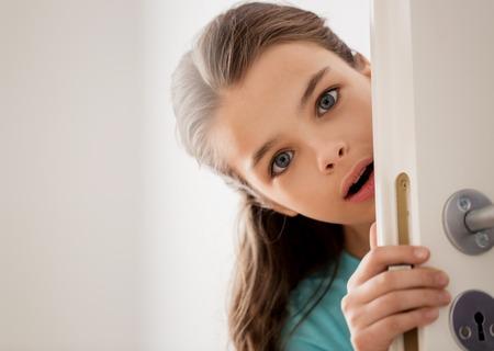 自宅のドアの後ろに隠れて怯えた美しい少女