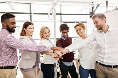 all smiles: happy business team with hands on top at office