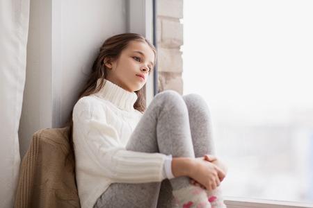 la infancia, la tristeza y el concepto de la gente - hermosa muchacha triste en el suéter sentado en el alféizar de la ventana en casa en invierno