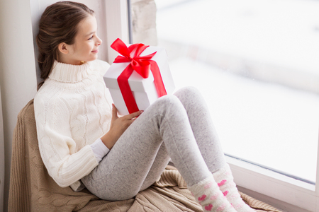 girl with gift sitting on sill at home window Stockfoto