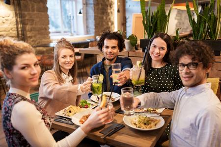 amigos felices con bebidas y comida en el restaurante