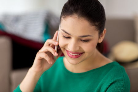 hispanic girl: happy woman calling on smartphone at home