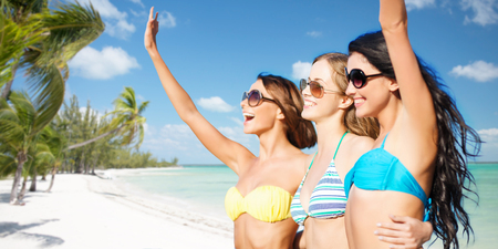 hands out: happy young women in bikinis on summer beach