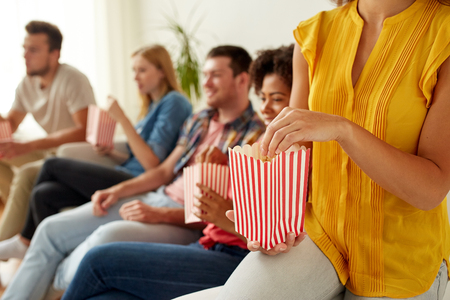binge: close up of happy friends eating popcorn at home Stock Photo