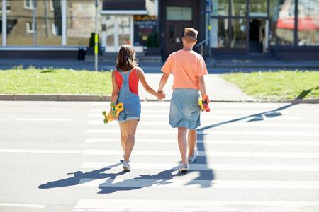 paso de peatones: pareja de adolescentes con monopatines en paso de peatones de la ciudad