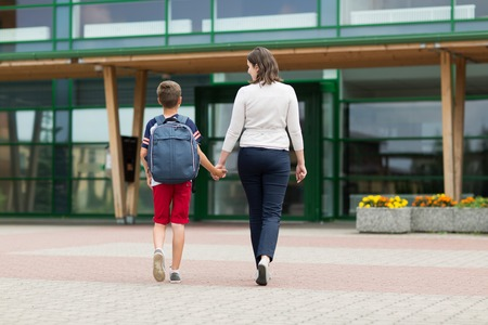 elementary student boy with mother going to school
