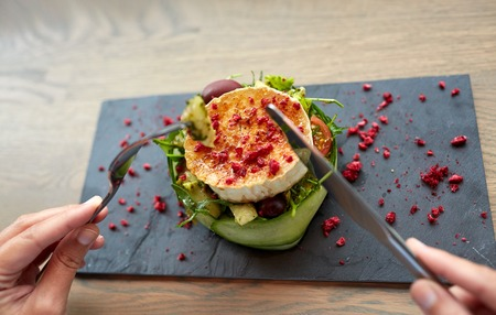 queso cabra: woman eating goat cheese salad at restaurant