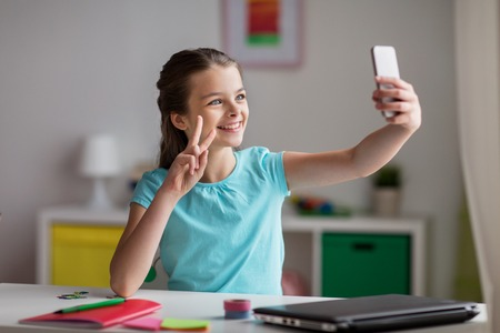 kids hand: happy girl with smartphone taking selfie at home Stock Photo