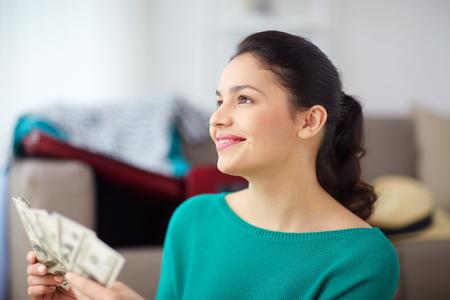 自宅に彼女の旅行の計画のお金で幸せな女 写真素材