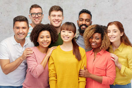 group of men: diversity, race, ethnicity and people concept - international group of happy smiling men and women over gray concrete background