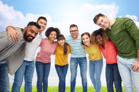 diversity, race, ethnicity and people concept - international group of happy smiling men and women hugging over blue sky background