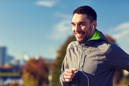 fitness, sport, people, technology and lifestyle concept - happy man running and listening to music in earphones at city