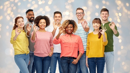 diversity, race, ethnicity and people concept - international group of happy smiling men and women showing ok hand sign over holidays lights background