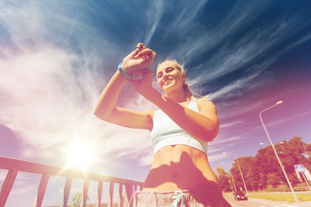 estilo de vida saludable: fitness, sport, people, technology and healthy lifestyle concept - smiling young woman with heart rate watch and earphones exercising outdoors Foto de archivo