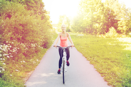 mujer alegre: fitness, sport, people and healthy lifestyle concept - happy young woman riding bicycle outdoors Foto de archivo