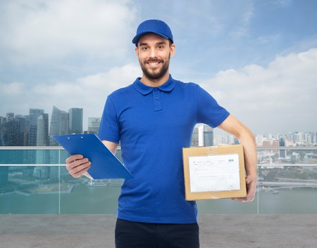 delivery service, mail, logistics, people and shipping concept - happy man with parcel box and clipboard over singapore city marina bay background