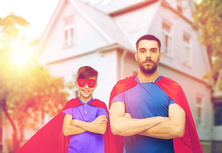 family, power and people concept - man and boy wearing mask and red superhero cape over house background Stock Photo